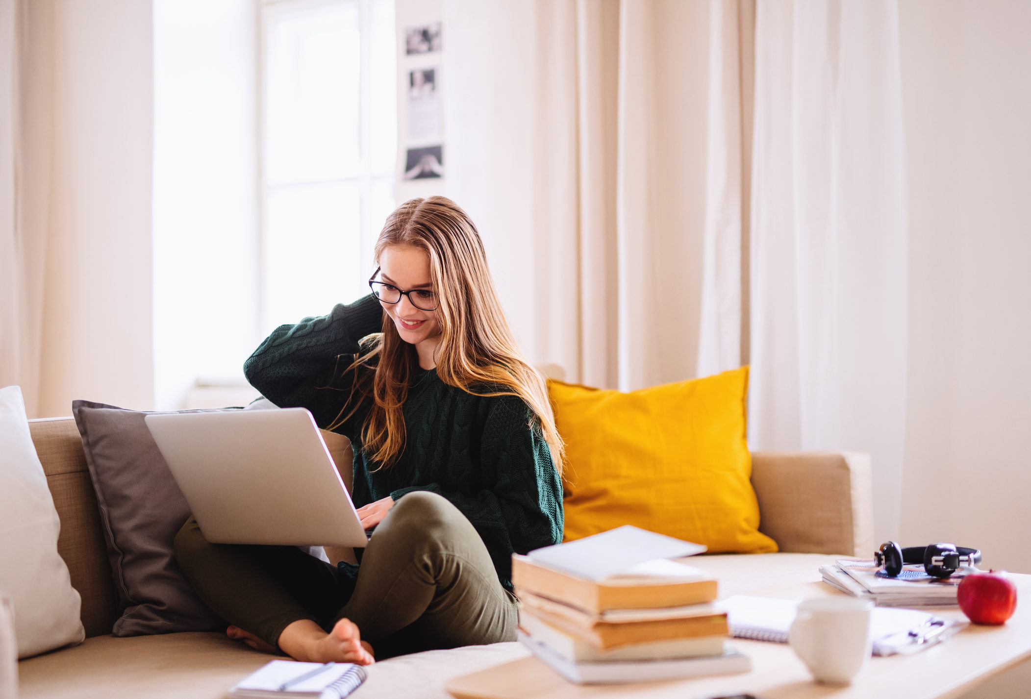 a-young-female-student-sitting-on-sofa-using-laptop-when-studying