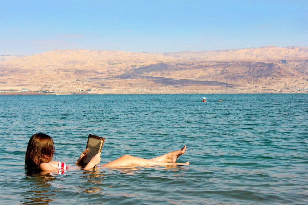 young-woman-reads-a-book-floating-in-the-dead-sea-in-israel